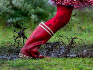 Rode laarzen stampen in de plassen