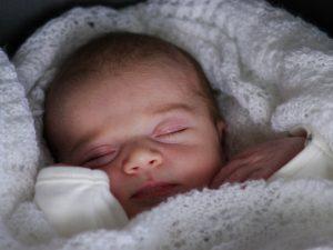 Slapende baby in witte deken