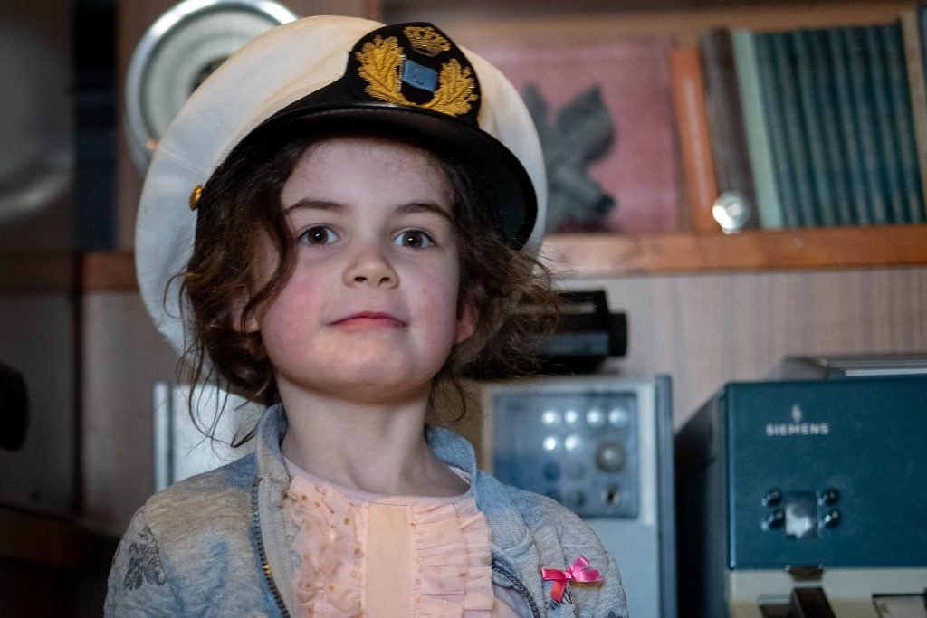 Girl wearing a captains hat at the museum IJmuiden