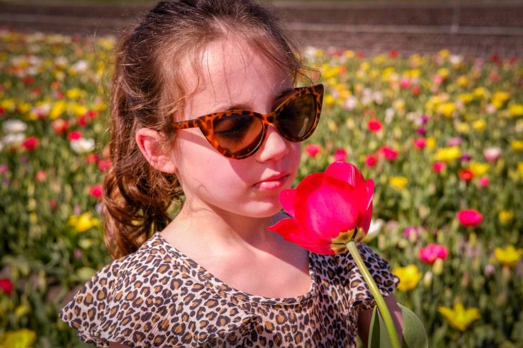 Girl smelling a flower at Annemiekes Pluktuin