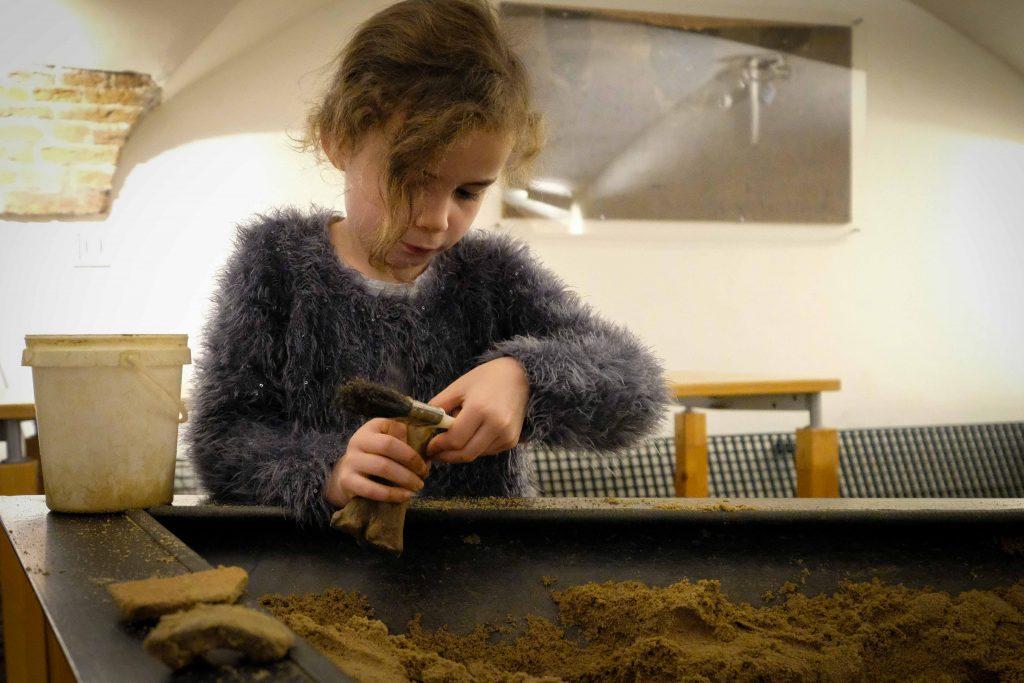 Meisje doet opgraving in Archeologisch Museum Haarlem