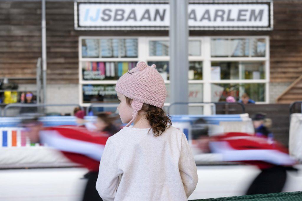 Meisje kijkt naar de 400 meterbaan bij IJsbaan Haarlem