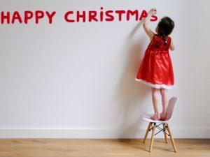 Meisje in kerstjurk schrijft Happy Christmas op de muur