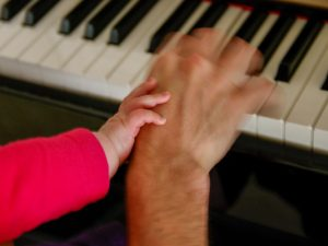 Handen van vader en baby op de piano