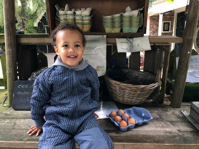 Jongetje met eieren bij een stalletje