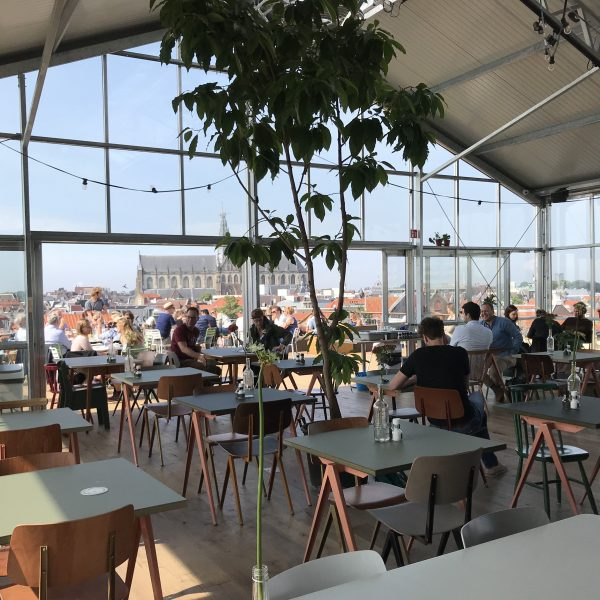 Mensen binnen en op terras bij DAKKAS Haarlem